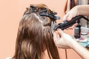 Bild von Friseur, der Haarverlängerung befestigt