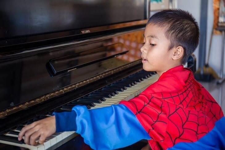 Bild von kleinem Jungem beim Klavier spielen
