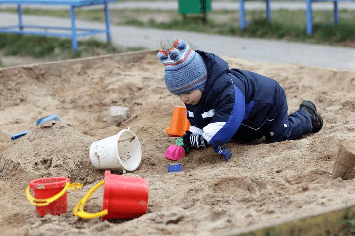 Bild von Kind beim Spielen im Sandkasten