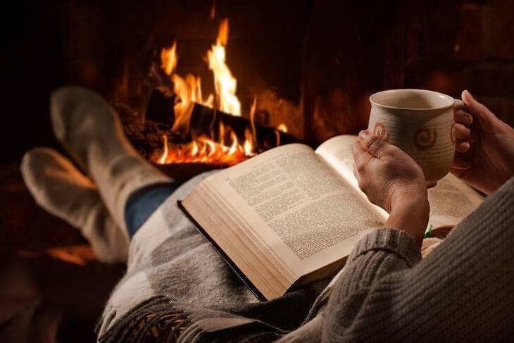 Bild von Frau mit Buch am Kaminfeuer
