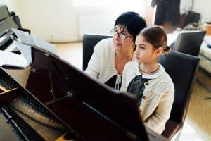 Bild von Mädchen beim Klavierunterricht