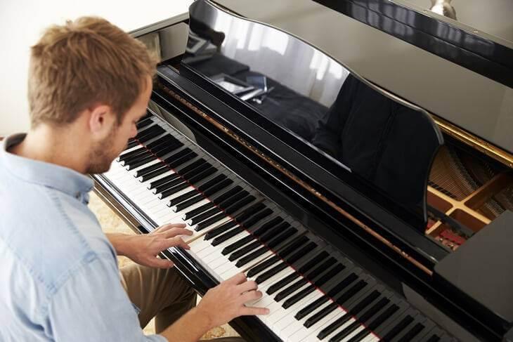 Bild von jungem Mann beim Klavier spielen