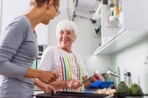 Bild von älterer Frau und Pflegekraft beim Kochen