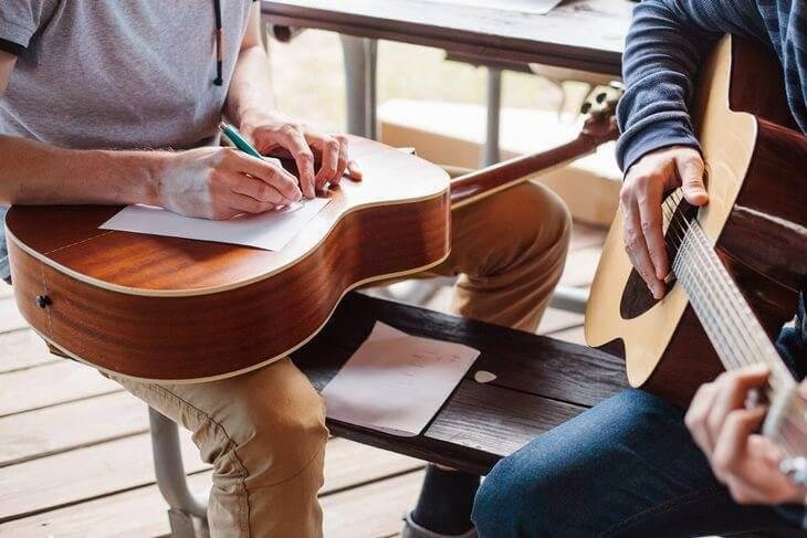 Bild von zwei Personen beim Gitarre spielen