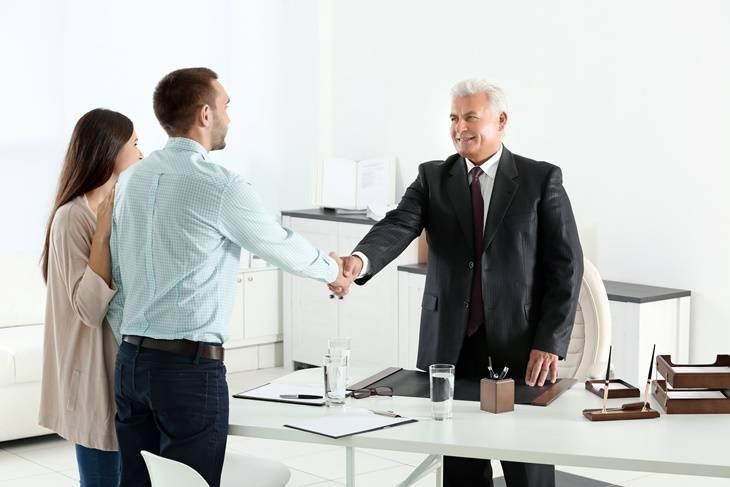Ein junges Paar (Mann und Frau) reichen ihrem Anwalt die Hand.