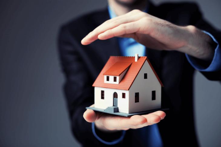 Ein Mann hält ein Modell-Haus in der rechten Hand und hält seine linke schützend darüber.