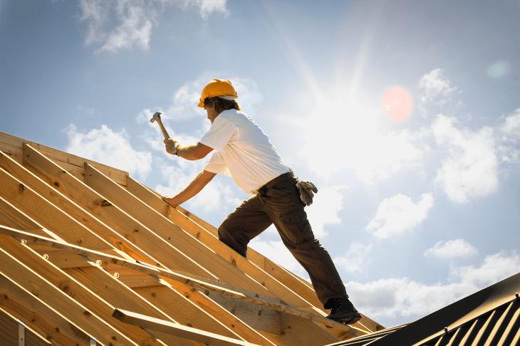 Ein Handwerker arbeitet an einem Dachstuhl.