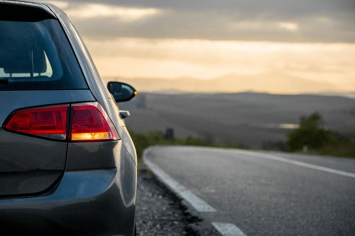 Ein Auto steht bei Sonnenuntergang am Straßenrand.