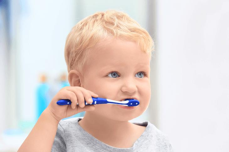 Bild von einem blonden Jungen, der sich die Zähne putzt